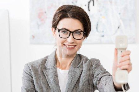 Photo pour Souriante séduisante femme d'affaires dans des verres montrant le combiné du téléphone fixe au bureau - image libre de droit