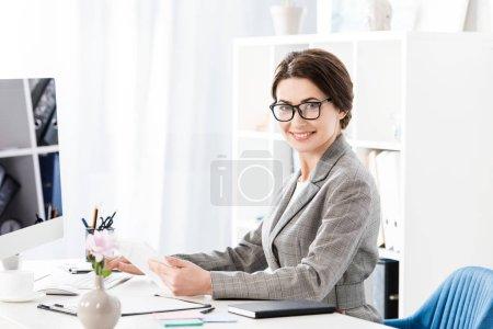 Foto de Sonriendo a empresaria atractiva celebración de tableta y sentado en la mesa con ordenador en la oficina - Imagen libre de derechos