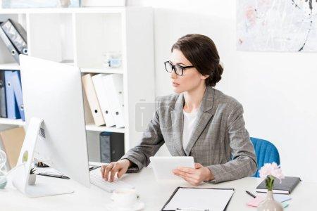 Photo pour Séduisante femme d'affaires en costume gris tenant la tablette et ordinateur de bureau en regardant - image libre de droit