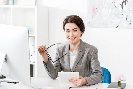smiling attractive businesswoman in grey suit holding glasses with tablet and looking at camera in office