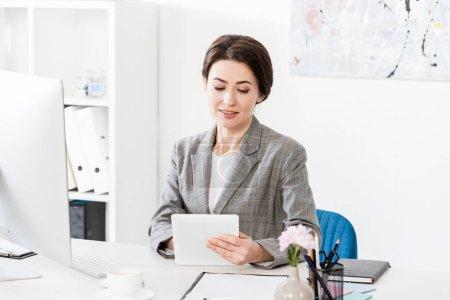 Photo pour Séduisante femme d'affaires en costume gris à l'aide de tablette à table dans le bureau - image libre de droit