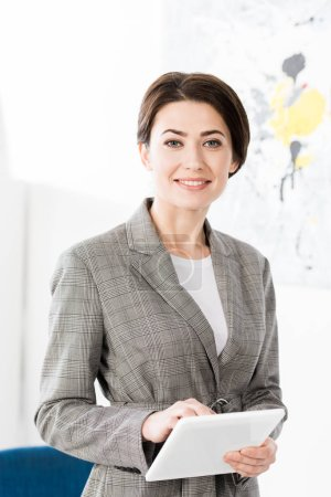 Photo for Portrait of smiling attractive businesswoman in grey suit holding tablet in office - Royalty Free Image