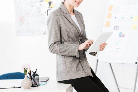 Photo pour Image recadrée de femme d'affaires en costume gris, assis sur la table et avec tablette bureau - image libre de droit