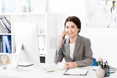 atractiva mujer de negocios en traje gris hablando por teléfono inteligente y sosteniendo la taza de café en la oficina