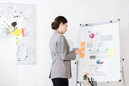 Photo pour Vue latérale d'une femme d'affaires attrayant en gris costume debout près de flipchart au bureau - image libre de droit