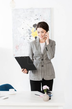 attractive businesswoman in grey suit talking by smartphone and holding clipboard in office