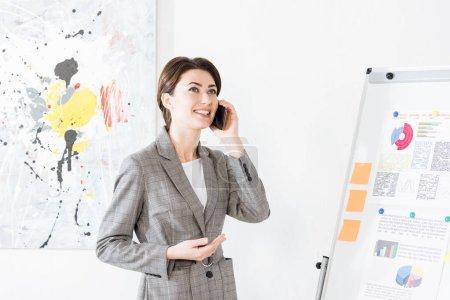 Photo pour Séduisante femme d'affaires en costume gris debout près de paperboard et parler de smartphone au bureau - image libre de droit