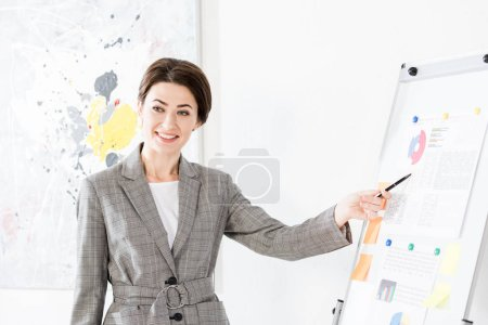 smiling beautiful businesswoman in grey suit pointing on flipchart during project presentation in office