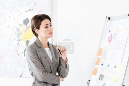 Photo for Pensive attractive businesswoman in grey suit looking at flipchart during project presentation in office - Royalty Free Image