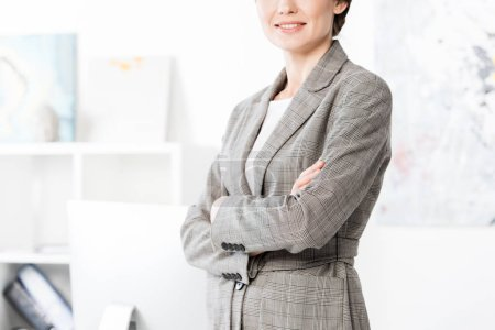 Photo for Cropped image of businesswoman in grey suit standing with crossed arms in office - Royalty Free Image
