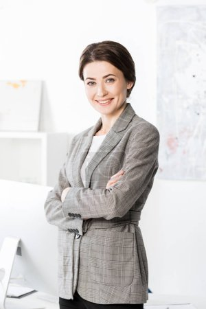 smiling attractive businesswoman in grey suit standing with crossed arms and looking at camera in office