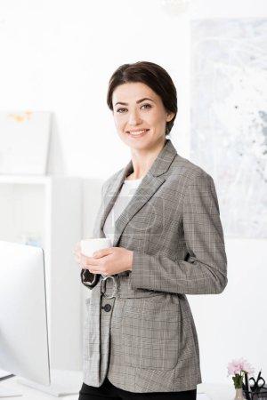 Photo pour Souriante séduisante femme d'affaires en costume gris tenant la tasse de café et de regarder la caméra dans le bureau - image libre de droit