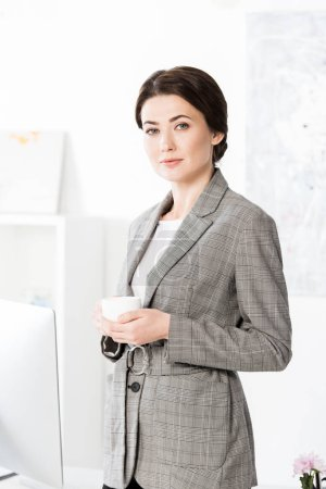 Photo for Attractive businesswoman in grey suit holding cup of coffee and looking at camera in office - Royalty Free Image