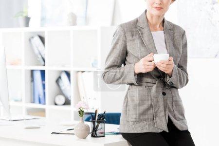 Photo pour Image recadrée d'une femme d'affaires en costume gris assise sur une table et tenant une tasse de café au bureau - image libre de droit