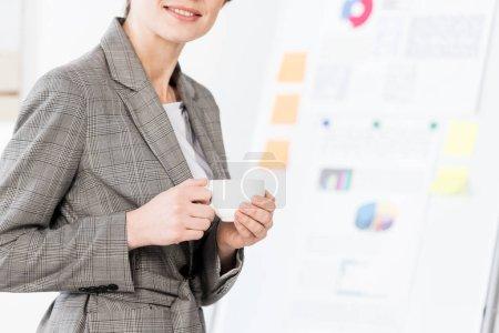 Photo pour Image recadrée femme d'affaires en costume gris tenant tasse de café au bureau - image libre de droit