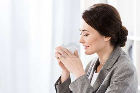 Photo pour Vue latérale d'une femme d'affaires attrayant en gris convenir à boire un café au bureau - image libre de droit