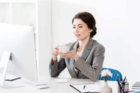 beautiful businesswoman in grey suit sitting at table with computer and holding cup of coffee in office