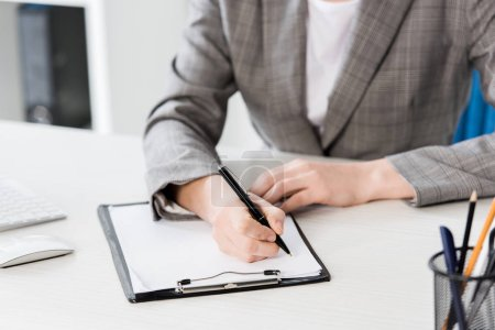 Photo for Cropped image of businesswoman in grey suit writing something to clipboard in office - Royalty Free Image