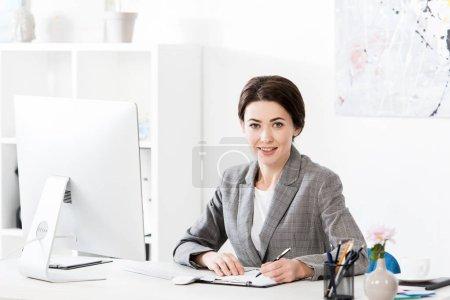 atractiva mujer de negocios en traje gris escribiendo algo al portapapeles en la oficina y mirando a la cámara