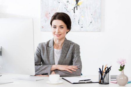attractive businesswoman in grey suit sitting at table with computer in office and looking at camera
