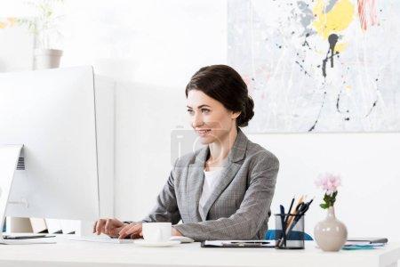 Photo pour Souriant attrayant femme d'affaires en costume gris assis en utilisant l'ordinateur dans le bureau - image libre de droit