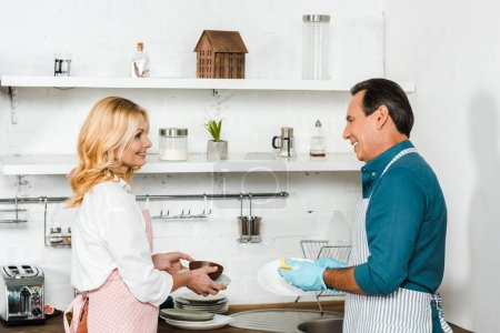 mature husband washing dishes and wife holding plates cooking in kitchen