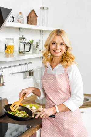 Photo for Smiling attractive mature woman frying vegetables in kitchen and looking at camera - Royalty Free Image