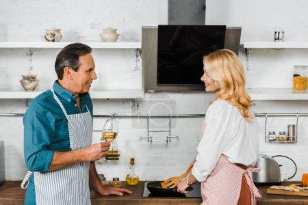 esposa madura freír verduras y marido sosteniendo vaso de vino en la cocina