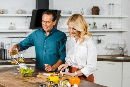 Photo for Mature wife cutting vegetables and husband pouring wine in glasses in kitchen - Royalty Free Image