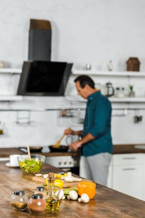 Photo for Selective focus of mature man frying vegetables in kitchen, spices on tabletop - Royalty Free Image