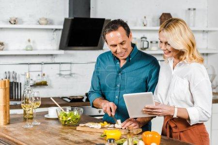 Photo pour Femme mature à l'aide de tablette et mari coupe légumes en cuisine - image libre de droit