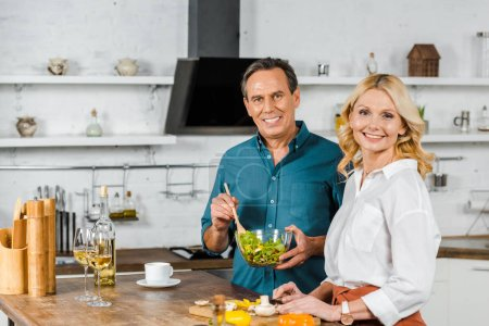 Photo for Happy mature wife and husband cooking salad together in kitchen, looking at camera - Royalty Free Image