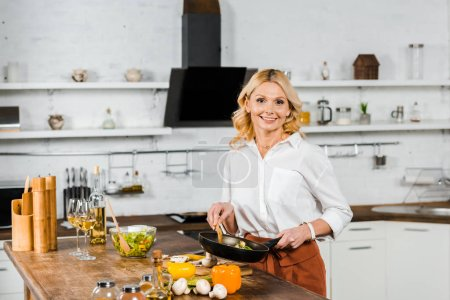 Photo for Smiling attractive mature woman holding frying pan with vegetables in kitchen and looking at camera - Royalty Free Image
