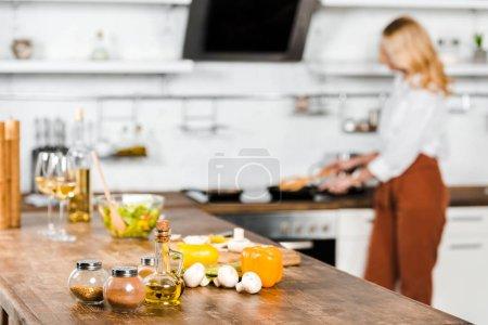 Photo pour Foyer sélectif de la femme mûre cuisine légumes sur poêle dans la cuisine, épices sur table - image libre de droit
