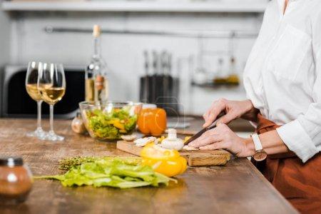 Photo pour Image recadrée d'une femme mûre coupant des légumes sur une planche en bois dans la cuisine - image libre de droit