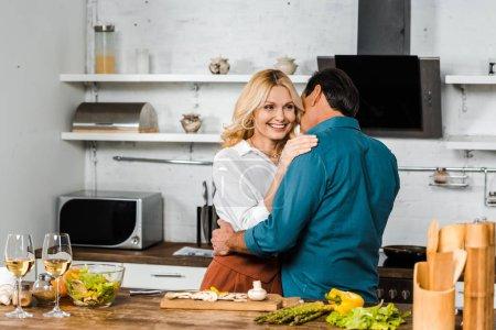 Photo pour Heureuse femme mature et mari hugging en cuisine - image libre de droit