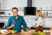 """Постер, картина, фотообои """"обжаривания овощей зрелой жены и мужа, держа бокал вина в кухне"""""""