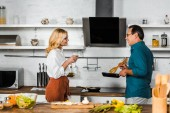 mature wife holding glass of wine and husband cooking at stove in kitchen