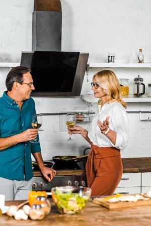 Photo pour Femme mature et mari tenant des verres de vin et se regardant dans la cuisine - image libre de droit