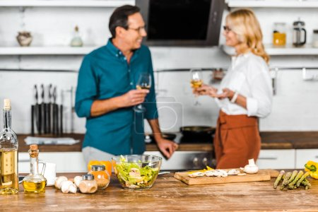 Photo for Selective focus of mature wife and husband holding glasses of wine and looking at each other in kitchen - Royalty Free Image