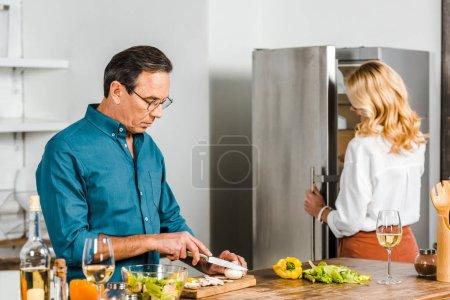 Photo pour Femme mature prendre quelque chose de réfrigérateur et mari légumes coupe dans cuisine - image libre de droit