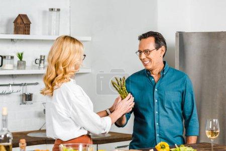 Photo pour Mari mature donnant des asperges à sa femme pour cuisiner dans la cuisine - image libre de droit