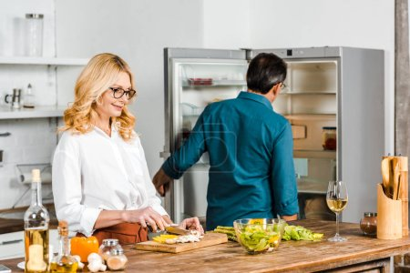 Photo for Mature wife cutting vegetables and husband looking at fridge in kitchen - Royalty Free Image