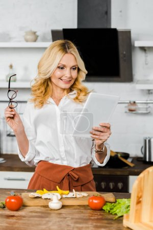 smiling attractive mature woman using tablet in kitchen
