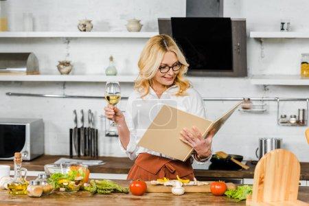 attraktive reife Frau mit einem Glas Wein und Blick auf Kochbuch in der Küche