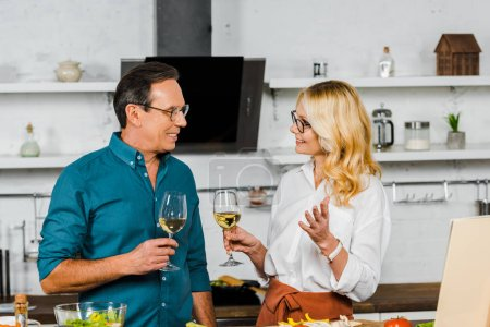 smiling mature wife and husband holding glasses of wine and talking in kitchen