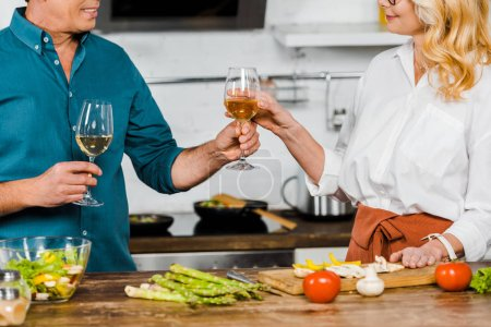 Photo pour Image recadrée de mari mature donnant un verre de vin à la femme dans la cuisine - image libre de droit