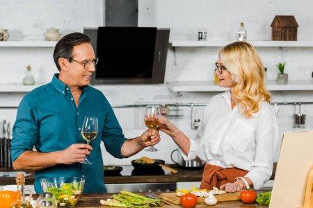 marido maduro dando copa de vino a la esposa en la cocina