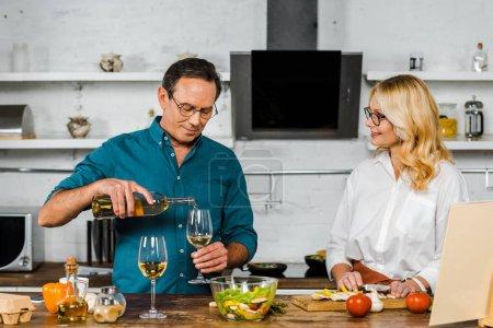 Photo pour Beau mari mature versant du vin dans des verres, femme coupant des légumes dans la cuisine - image libre de droit