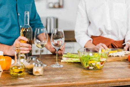 Photo pour Image recadrée de femme mature coupant des légumes et mari tenant bouteille de vin dans la cuisine - image libre de droit